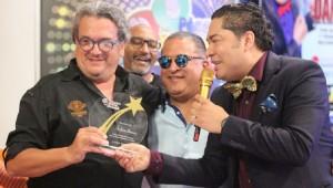 Juan Basanta mientras recibía su reconocimiento de parte de Frederick Martínez. Foto: Fuente externa